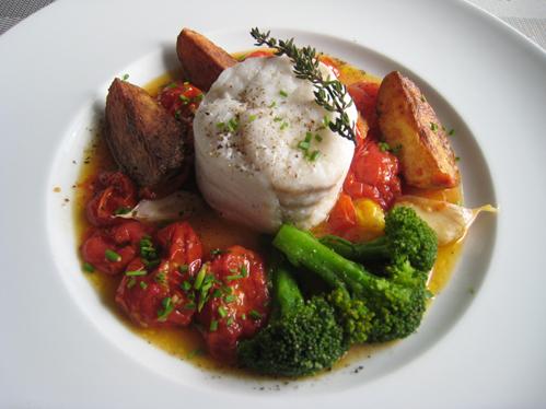 Gedämpftes Skreifilet aufrecht serviert mit Schmortomaten und Brokkoli