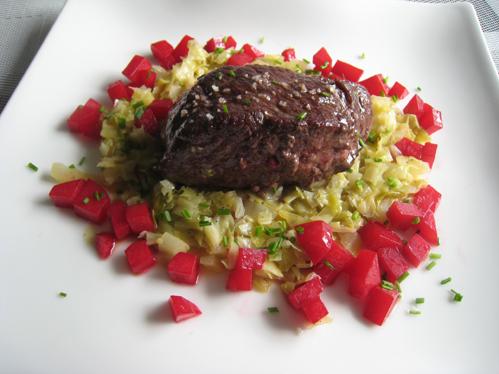 Straußensteak auf Spitzkohlschlotze mit roten Kartoffelwürfeln