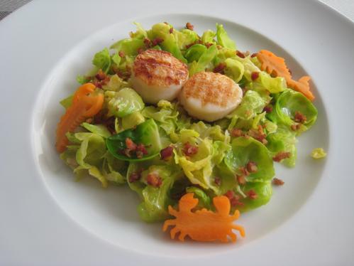 Jakobsmuschelnüsschen und Speckwürfel auf warmem Salat von Rosenkohlblättern