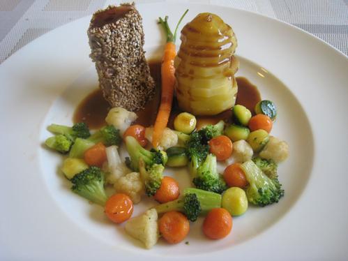 Frischlingsrücken im Sesammantel an einer Kartoffelpyramide und buntem Gemüse