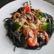 Meeresfrüchte im schwarzen Pastanest mit Muschelsauce