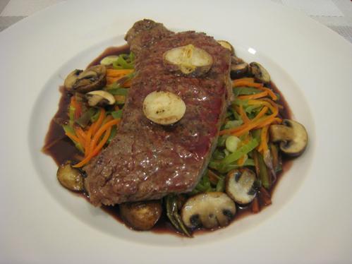 Rumpsteak auf Bohnen- und Möhrenstreifen mit Champignons in einer Rotweinsauce