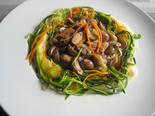 Champignons in einem Nest von Rettich-, Möhren- und Zucchininudeln