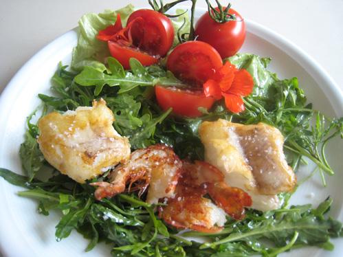 Seeteufelmedaillons und Garnelen mit kleinen Tomaten auf Rucola