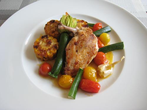 Hähnchenbrust auf der Haut gebraten mit gefüllter Zucchiniblüte, gebratenen Maisscheiben und geschmorten Tomaten