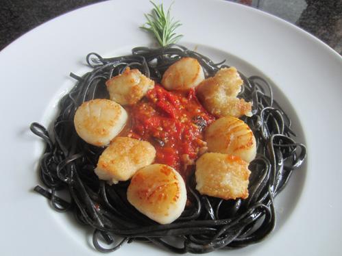 Seeteufelfilet und Jakobsmuscheln auf schwarzer Pasta mit Tomaten-Oliven-Kompott